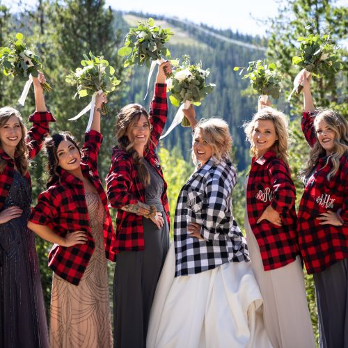 Bridal party in flannel shirts over their dresses