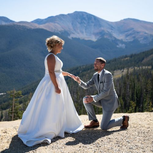 Groom on one knee with mountains in background